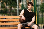 "Постер, картина, фотообои ""serious basketball player with ball sitting on wooden bench in sunny day at basketball court """