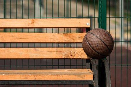 Photo pour Balle de basket marron sur banc en bois au terrain de basket - image libre de droit