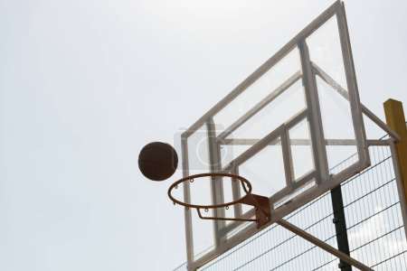 Photo for Ball and basketball hoop under sky in sunny day - Royalty Free Image