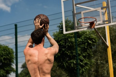 back view of shirtless basketball player throwing ball in basket at basketball court