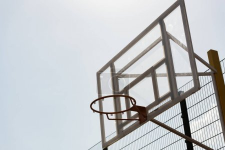 Photo for Basketball hoop at basketball court under sky in sunny day - Royalty Free Image