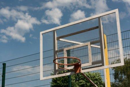 Photo pour Cerceau de basket-ball au terrain de basket-ball sous le ciel nuageux bleu - image libre de droit