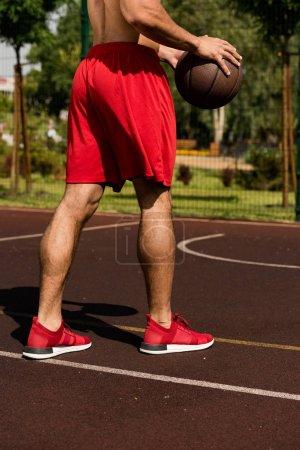 Photo pour Vue partielle du joueur de basket-ball avec la bille au terrain de basket-ball dans la journée ensoleillée - image libre de droit