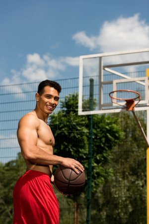 Photo for Shirtless mixed race basketball player with ball looking at camera at basketball court - Royalty Free Image