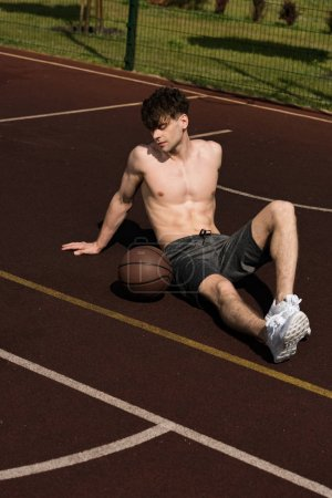 Photo for Sexy shirtless basketball player with ball sitting at basketball court - Royalty Free Image