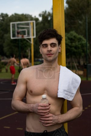 Photo for Sexy shirtless sportsman with towel holding bottle of water at basketball court - Royalty Free Image