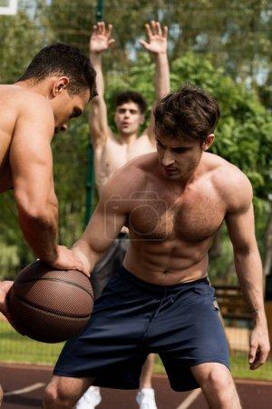 Foto de Shirtless sportsmen playing basketball at basketball court in sunny day - Imagen libre de derechos