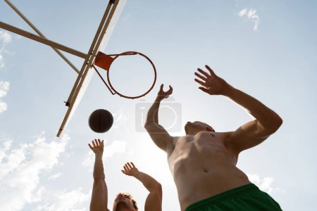 Photo for Bottom view of shirtless basketball players throwing ball in basket in sunny day - Royalty Free Image