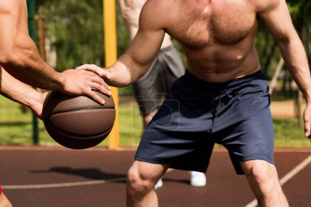 Photo for Partial view of shirtless sportsmen playing basketball at basketball court - Royalty Free Image