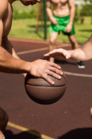 Foto de Partial view of shirtless sportsmen playing basketball at basketball court - Imagen libre de derechos