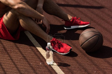 Photo for Partial view of sportsman in red sneakers sitting at basketball court with bottle of water and ball in sunny day - Royalty Free Image