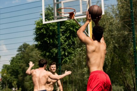 Photo for Shirtless sportsmen playing basketball at basketball court in sunny day - Royalty Free Image