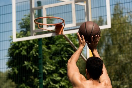 Photo for Back view of basketball player throwing ball in basket at basketball court - Royalty Free Image