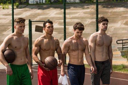 Photo pour Quatre joueurs de basket sexy torse nu avec des balles au terrain de basket - image libre de droit