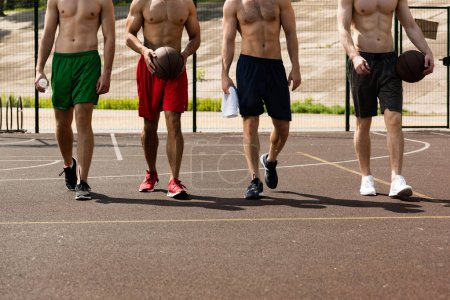 Foto de Cropped view of four shirtless basketball players with balls at basketball court - Imagen libre de derechos