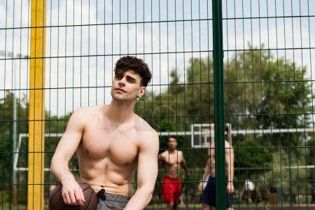 Photo for Pensive shirtless basketball player with ball standing at basketball court in sunny day - Royalty Free Image