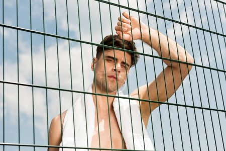 shirtless sportsman with white towel standing behind lattice at basketball court in sunny day