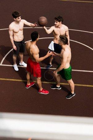 Photo pour Vue aérienne de quatre joueurs de basket-ball torse nu avec la bille au terrain de basket-ball - image libre de droit