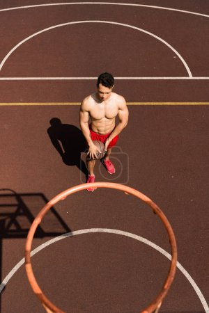 Photo for Overhead view of sexy shirtless mixed race basketball player with ball at basketball court - Royalty Free Image
