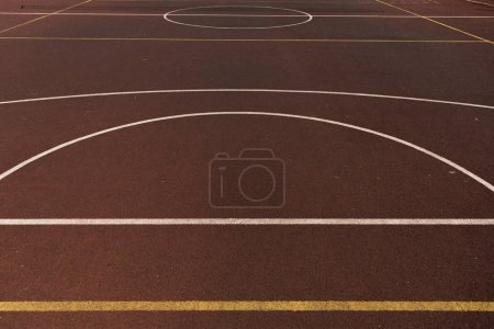 Photo for Basketball court with on yellow and white lines on brown playing surface - Royalty Free Image