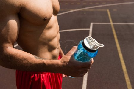 Photo for Partial view of shirtless muscular sportsman holding sport bottle at basketball court - Royalty Free Image
