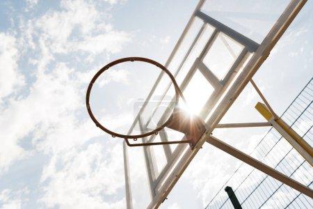 Photo pour Vue inférieure du backboard de basket-ball sous le ciel bleu avec des nuages dans la journée ensoleillée - image libre de droit