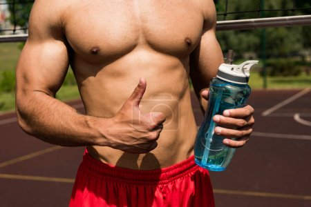 Photo for Partial view of shirtless muscular sportsman holding sport bottle and showing thumb up at basketball court - Royalty Free Image