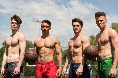 Photo pour Quatre joueurs de basket-ball sexy torse nu avec des balles au terrain de basket-ball dans la journée ensoleillée - image libre de droit