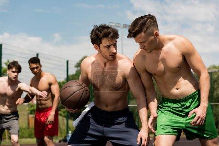 Foto de Shirtless muscular sportsmen playing basketball at basketball court under blue sky - Imagen libre de derechos