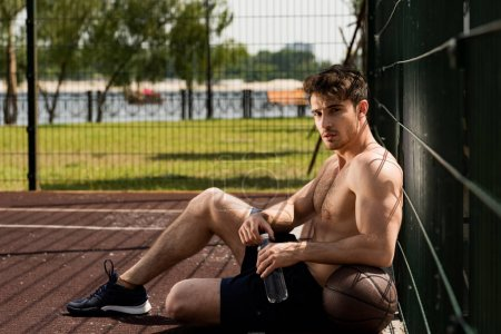 Photo for Sexy muscular sportsman with ball and bottle of water sitting at basketball court - Royalty Free Image