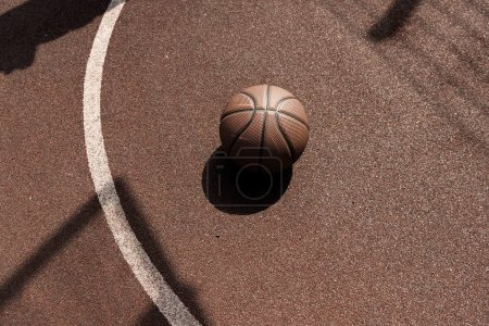 Photo for Ball on brown playing surface at basketball court - Royalty Free Image