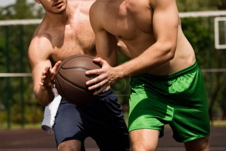 Foto de Partial view of two shirtless sportsmen playing basketball at basketball court in sunny day - Imagen libre de derechos