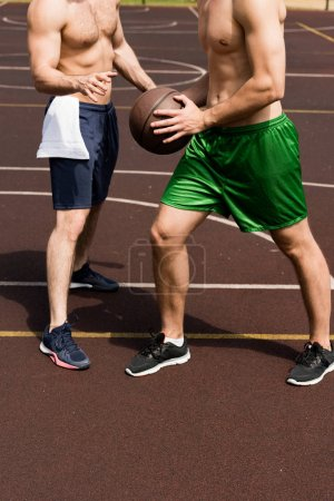 Photo for Partial view of two shirtless sportsmen playing basketball at basketball court in sunny day - Royalty Free Image