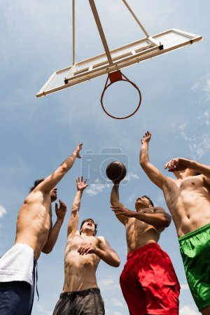 Photo for Bottom view of shirtless sportsmen playing basketball under blue sky - Royalty Free Image