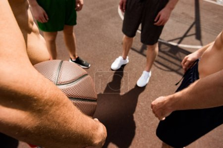 Photo for Cropped view of four sportsmen with ball at basketball court - Royalty Free Image