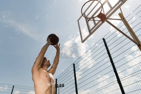 Photo for Sexy shirtless basketball player throwing ball in basket at basketball court - Royalty Free Image
