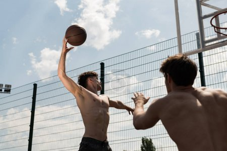 Photo for Two sexy shirtless sportsmen playing basketball under blue sky at basketball court - Royalty Free Image