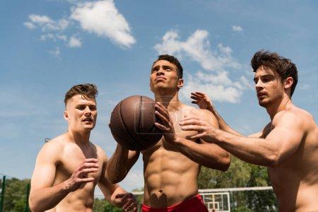 Foto de Three sexy shirtless sportsmen playing basketball under blue sky - Imagen libre de derechos