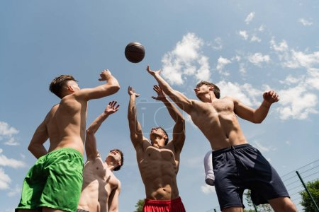 Foto de Four sexy shirtless sportsmen playing basketball under blue sky - Imagen libre de derechos