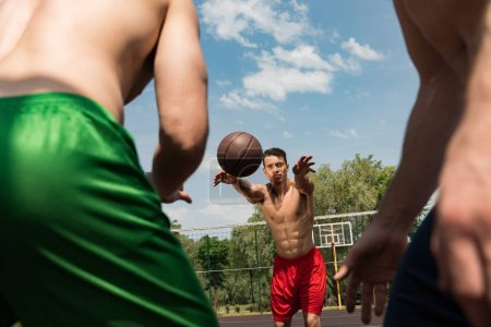 Photo for Cropped view of sexy shirtless sportsmen playing basketball under blue sky - Royalty Free Image