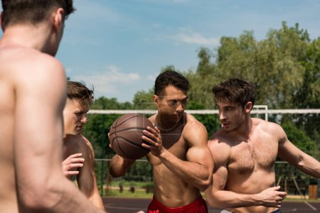 cropped view of sexy shirtless sportsmen playing basketball under blue sky