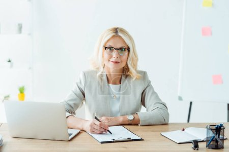Photo for Cheerful woman holding pen near clipboard and laptop in office - Royalty Free Image