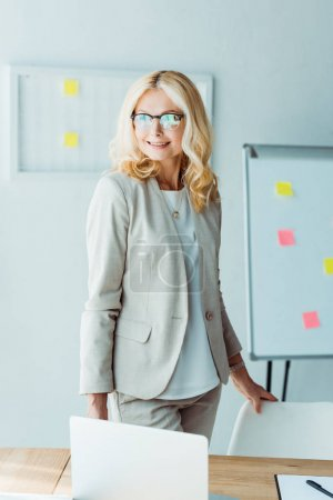 Photo for Cheerful blonde woman standing near table and touching chair in office - Royalty Free Image