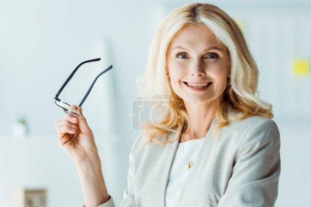 Photo pour Femme blonde gaie retenant des glaces et regardant l'appareil-photo - image libre de droit