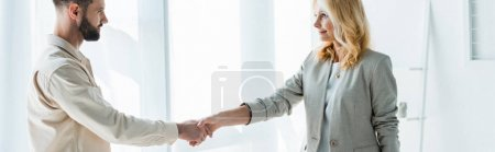 Photo for Panoramic shot of recruiter and handsome employee shaking hands - Royalty Free Image