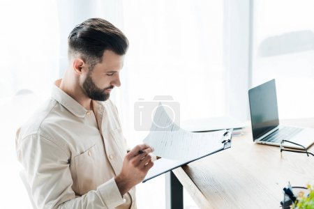 handsome bearded man looking at paper while holding clipboard