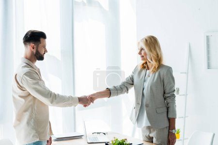 Photo for Attractive blonde recruiter and handsome employee shaking hands - Royalty Free Image