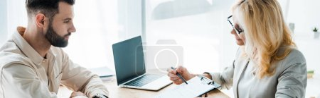 Photo for Panoramic shot of recruiter in glasses holding pen near clipboard and looking at bearded man - Royalty Free Image