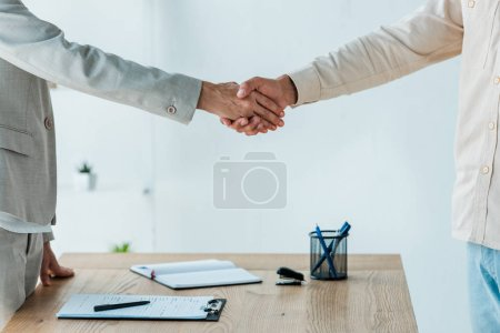cropped view of man and recruiter shaking hands near table
