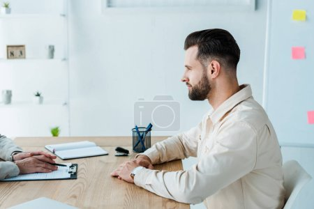 cropped view of recruiter near handsome bearded employee